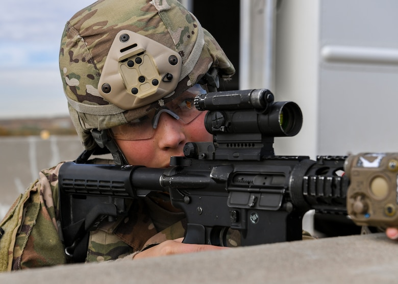 A security forces member looks down her scope.