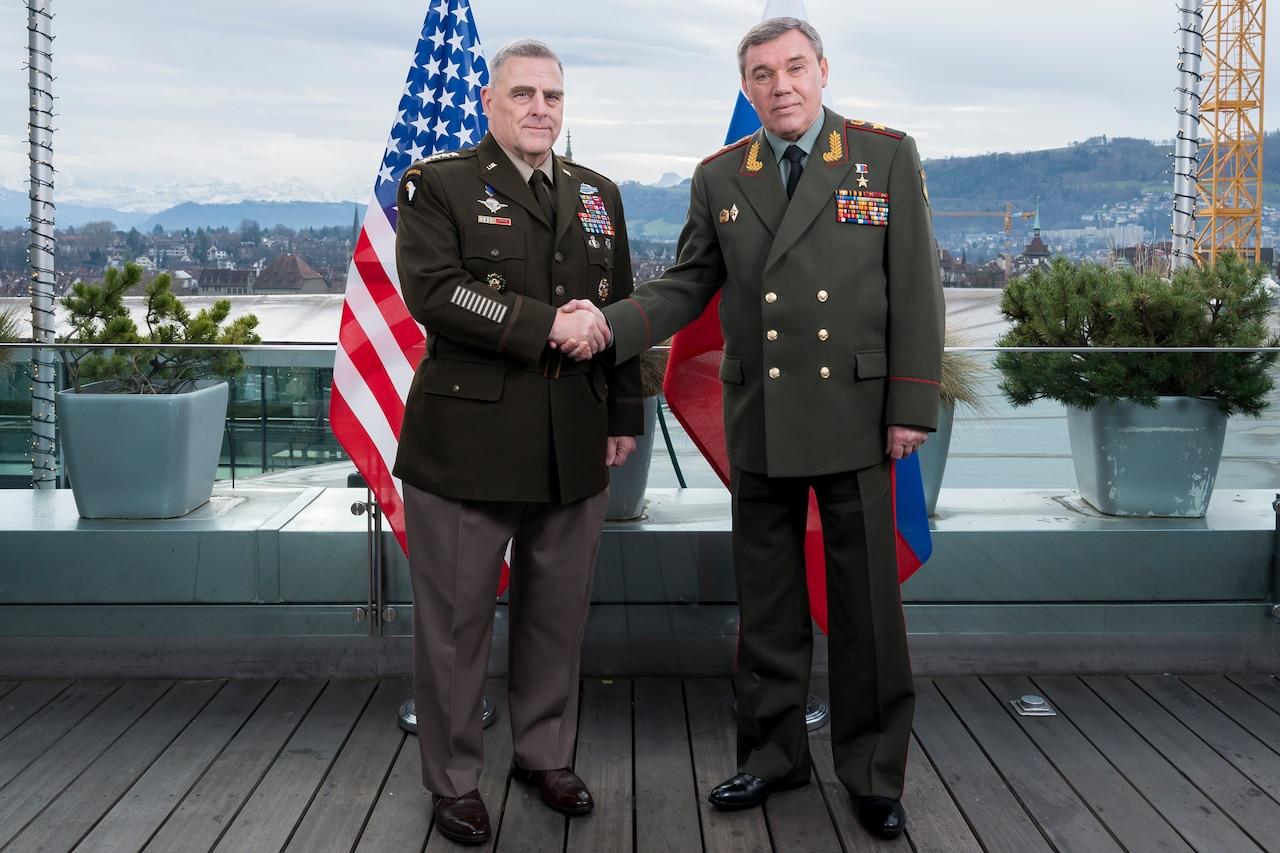 U.S. and Russian generals stand in front of their respective nations' flags and shake hands.