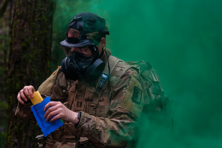 A soldier wears a gas mask while holding a blue envelope as green smoke surrounds.