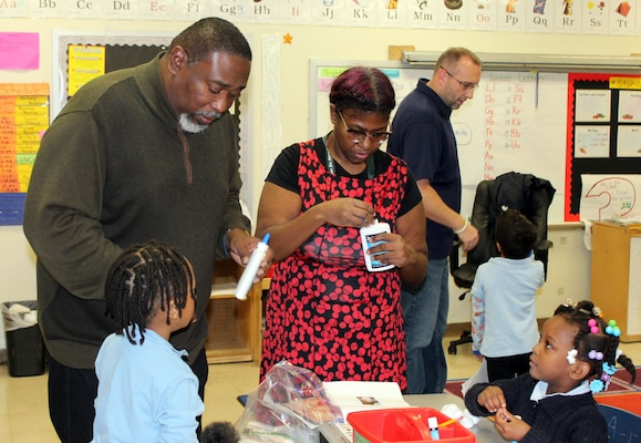DLA Troop Support volunteers help students make ornaments during the DLA Troop Support Children's Holiday Party Dec. 12, 2019 in Philadelphia.