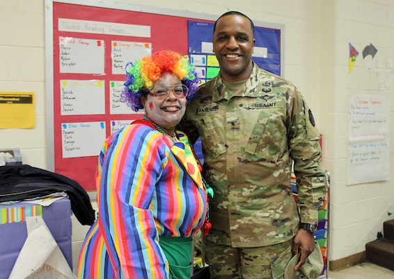 Crystal Robinson, a DLA Troop Support volunteer, left, and Army Brig. Gen. Gavin Lawrence, DLA Troop Support commander, right, pose for a photo during the Children's Holiday Party Dec. 12, 2019 in Philadelphia.