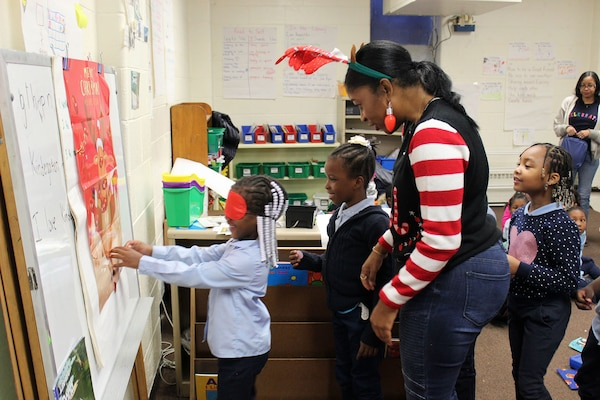 A DLA Troop Support volunteer helps children play games during the annual Children's Holiday Party Dec. 12, 2019 in Philadelphia.