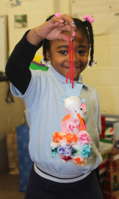 A student shows an ornament that was made during the DLA Troop Support Children's Holiday Party Dec. 12, 2019 in Philadelphia.
