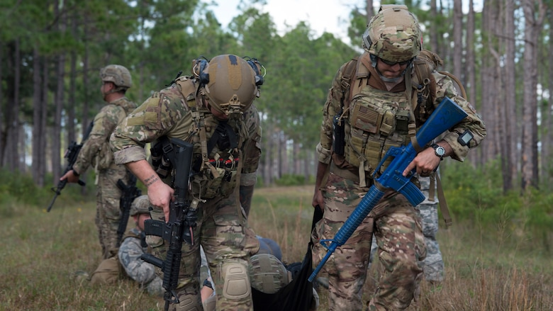 U.S. Air Force Staff Sgt. Taylor Lahteine, a 6th Civil Engineer Squadron explosive ordnance disposal (EOD) flight technician, and Staff Sgt. Ronnie Perez, a 927th Aeromedical Staging Squadron aeromedical technician, pull a simulated casualty to safety during a field training exercise Dec. 11, 2019, at Avon Park Air Force Range, Fla.  Lahteine and Perez provided tactical combat casualty care, such as tourniquet application, wound dressing and administering intravenous fluids during a simulated threat.