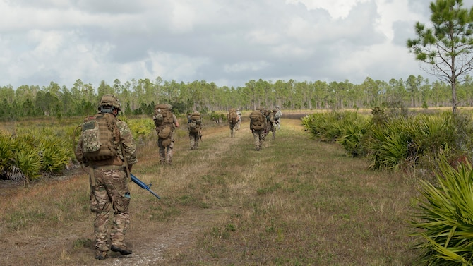 U.S. Air Force Airmen from the 6th Civil Engineer Squadron explosive ordnance disposal flight, the 6th Security Forces Squadron and the 927th Aeromedical Staging Squadron ruck march through Avon Park Air Force Range, Fla., Dec. 11, 2019.  The Airmen carried rucksacks weighing 35 to 50 pounds during a field training exercise to simulate real-world deployment operations.
