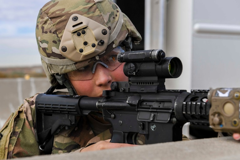 An airman looks through a view finder on a rifle.