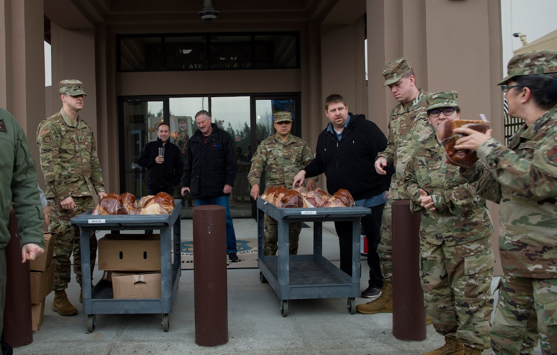 Western Air Defense Sector Airmen carry hams to a cart during Operation Ham Grenade at Joint Base Lewis-McChord, Wash., Dec. 17, 2019. More than 300 hams were donated to McChord Field Airmen by the Air Force Association McChord Field Chapter and Pierce Military Business Alliance. (U.S. Air Force photo by Senior Airman Tryphena Mayhugh)