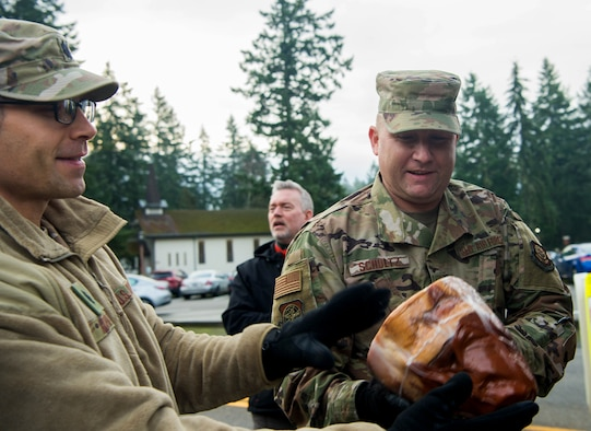 Chief Master Sgt. Rob Schultz, 62nd Airlift Wing command chief, passes along a ham during Operation Ham Grenade at Joint Base Lewis-McChord, Wash., Dec. 17, 2019. More than 300 ham were donated to Team McChord Airmen for them and their families during the holidays. (U.S. Air Force photo by Senior Airman Tryphena Mayhugh)