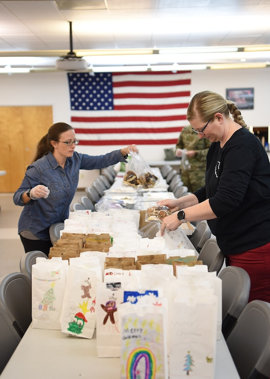 Vandenberg Air Force Base Spouse's Club members bag cookies for the 2019 Cookie Drive Dec. 16, 2019, at VAFB, Calif. During the drive, VAFB Spouse's Club members packaged cookies in bags decorated by students from local schools and delivered the bags to Airmen across the base.  (U.S. Air Force photo by Airman 1st Class Hanah Abercrombie)