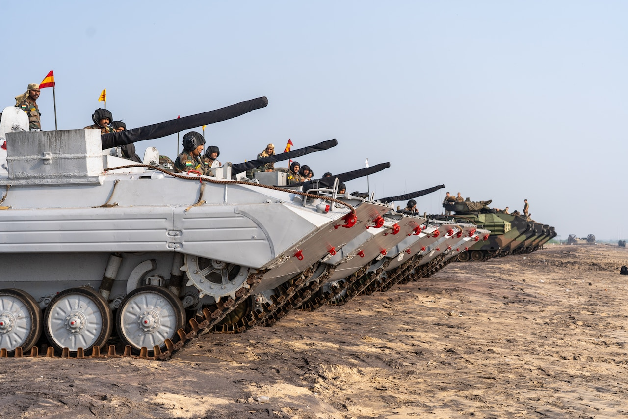 A handful of military tanks are lined up on the sand.