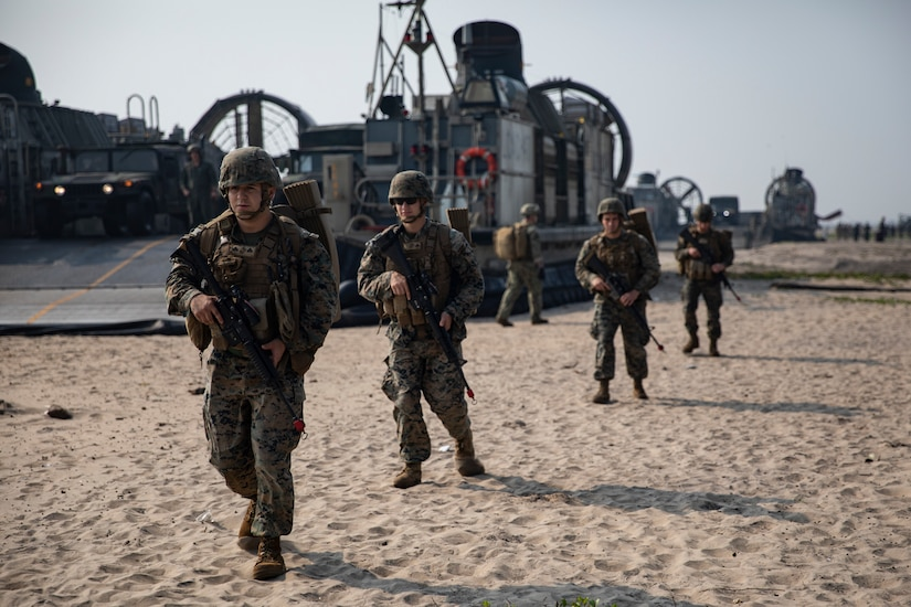 Service members walk across sand and carry rifles.  In the background is a large hovercraft military vehicle.