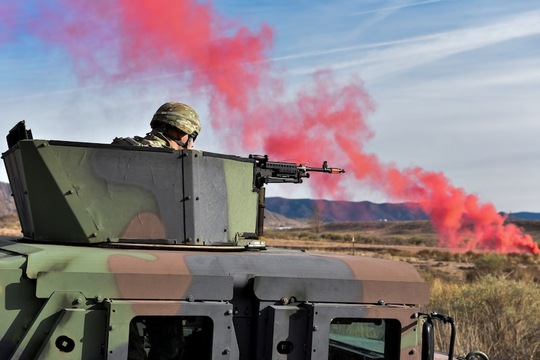 A security forces member in a humvee aims a M240B machine gun at opposing forces during training.