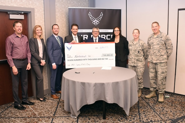 Col. James Smith, 50th Space Wing commander and Col. Laurel Walsh, 50th Operations Group commander receive a check for $750,000 during the Space Pitch Day event at Hilton Union Square Hotel in San Francisco in November. Capt. Jay-Sue Veatch, Chief of the 50th Space Wing combat development division said Schriever received $6 million for their pitches during the two-day event. (U.S. Air Force courtesy photo by Capt. Jay-Sue Veatch)