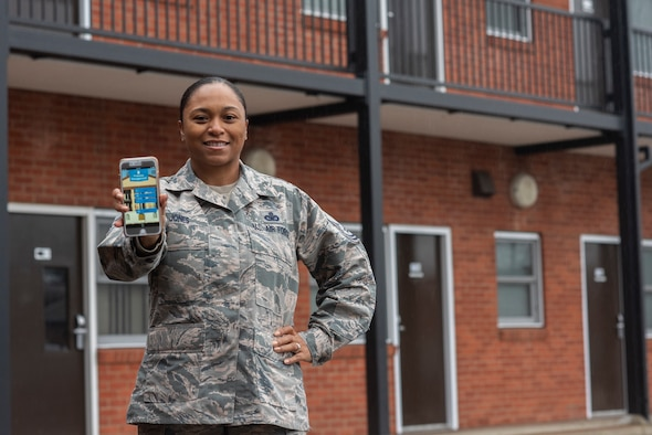 Master Sgt. Erika Jones, 100th Civil Engineer Squadron airmen dorm leader superintendent, displays the dorm app she designed at RAF Mildenhall, England, Dec. 17, 2019. Airmen living in the dorms can benefit from the improved process the app provides for submitting work order requests. (U.S. Air Force photo by Airman 1st Class Joseph Barron)