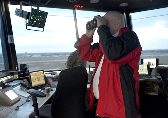 """William """"Doc"""" Schmitz, Commander-in-Chief for Veterans of Foreign Wars, peers through binoculars while touring the RAF Mildenhall control tower during a visit to base Dec. 18, 2019. Schmitz spoke with Airmen and toured Mildenhall to learn of the base's mission and quality of life programs. (U.S. Air Force photo by Senior Airman Brandon Esau)"""