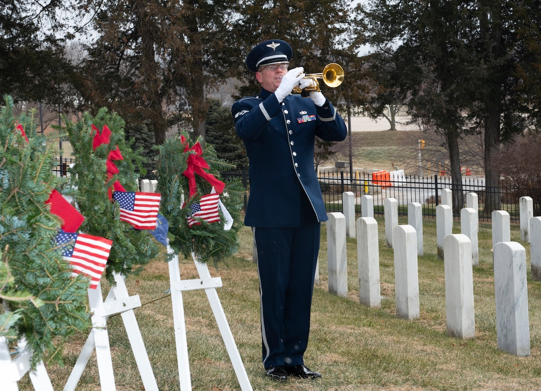 A photo of Staff Sgt. Daniel Thrower, Heartland of America Band, playing taps during National Wreaths Across America Ceremony at Offutt Air Force Base
