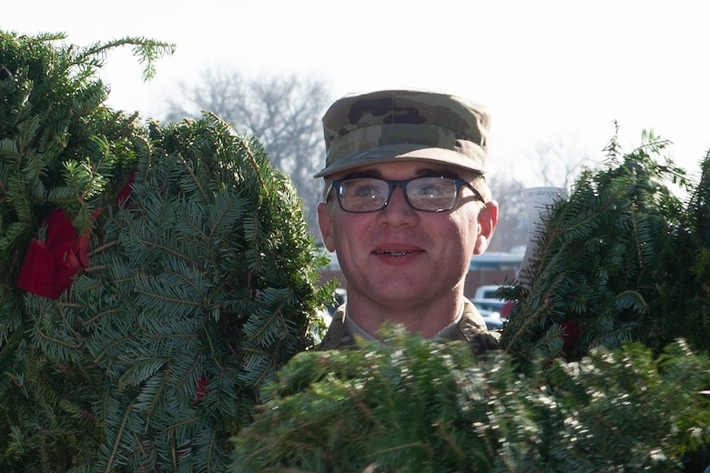 A photo of A volunteer carrying wreaths at at Offutt Air Force Base.