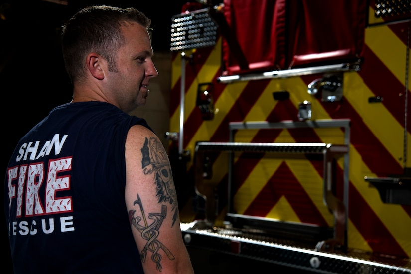 Photo of a Team Shaw members displaying a tattoo representing the fire and life-saving aspects of his job