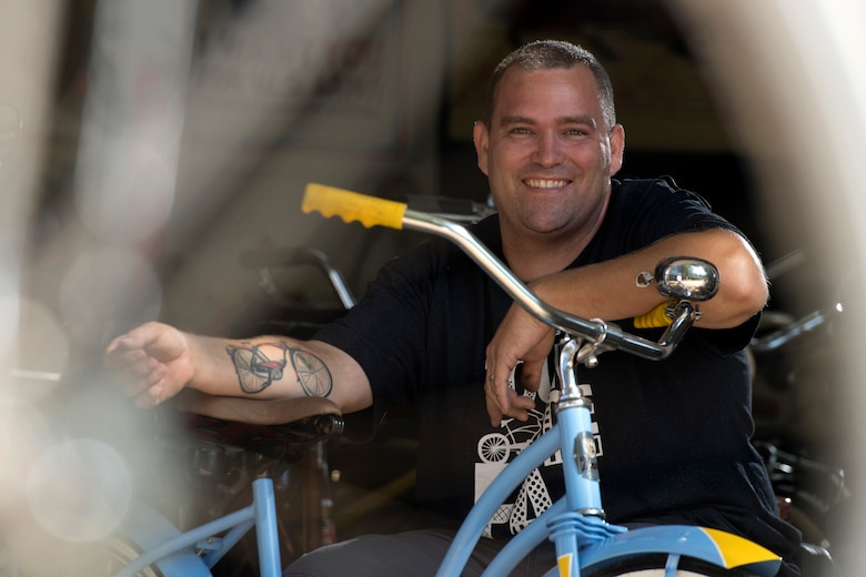 Photo of an Airman displaying a tattoo of his father's bicycle