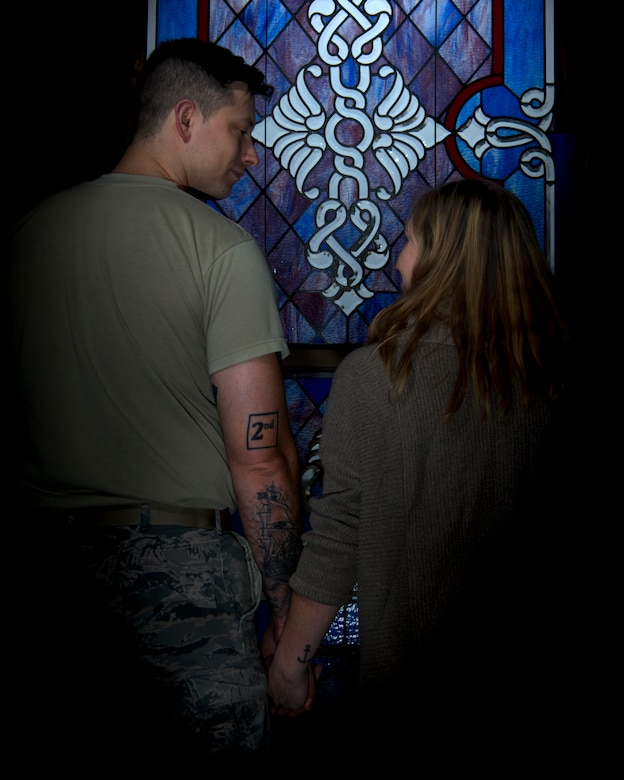 Photo of an Airman and his wife displaying their marriage tattoos