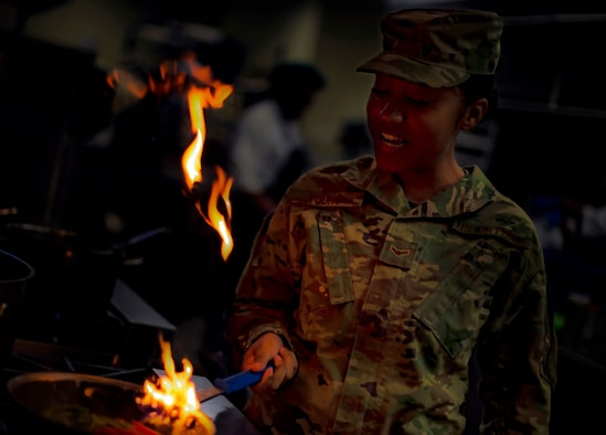 A military member in a utility uniform sautes vegetables in a frying pan. Flames shoot up, illuminating her face.