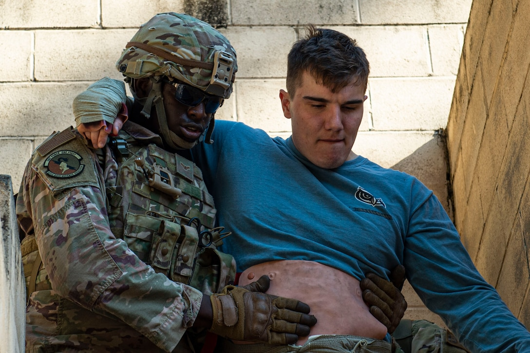 Photo of an Airman assisting a simulated victim during the Combat Lifesavers Course