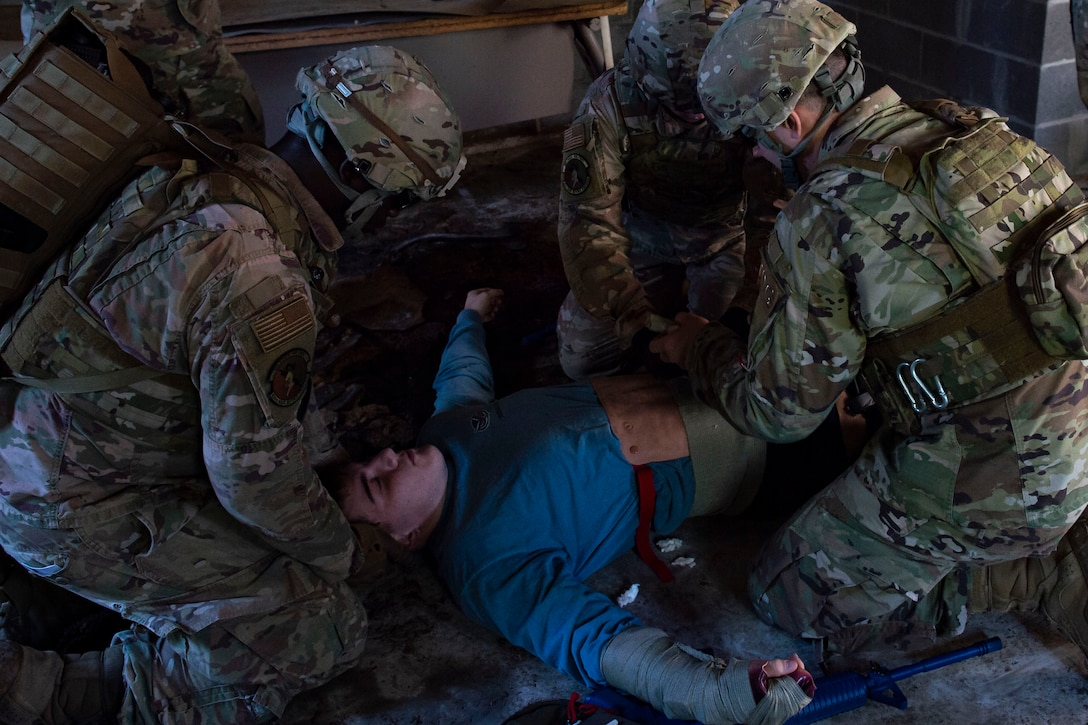 Photo of Airmen assess a simulated victim during the Combat Lifesavers Course.