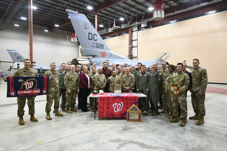Airmen from the 113th Wing, District of Columbia Air National Guard, pose for a group photo with Washington Nationals staff and the World Series trophy, during a display event at Joint Base Andrews, Md., Dec. 17, 2019. The 113th Wing presented Ryan Zimmerman, Washington Nationals first baseman, with a certificate and flag that was flown by the unit over the nation's capital. (U.S. Air Force photo by Airman 1st Class Spencer Slocum)