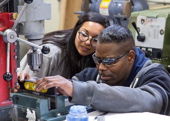 A Continuous Training and Development program instructor watches a worker check the level on a drilling project.