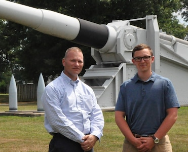 """IMAGE: DAHLGREN, Va. (July 12, 2019) – U.S. Naval Academy Midshipman Jonathon Copley and his mentor, Mike Burchik, a Naval Surface Warfare Center Dahlgren Division (NSWCDD) scientist, are pictured in front of a U.S. Navy 16-inch battleship gun on the parade field near NSWCDD headquarters during Copley's summer internship. While assigned to the Submarine Launched Ballistic Missile Program (SLBM), Copley worked with a team that supported developers who wrote code for the SLBM Fire Control System. """"I was astonished to see how many people were on the base working hard to keep our Navy on the cutting edge while maintaining the technology gap with our adversaries,"""" said Copley. """"They are working day in and day out to enhance the Navy's warfighting ability. It made me proud to know I will be joining a fighting force with such superb people behind it."""" (U.S. Navy photo/Released)"""
