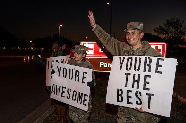 "From right, Lt. Col. Raymundo Vann, 323rd Training Squadron commander, Capt. Jessica Stanley, 737th Training Group and Lydia Davidson, wife of Col. Isaac Davidson, Inter-American Air Forces Academy commandant, hold positive messages of support at a base gate during the morning inbound commute as part of their new initiative, ""We Care,"" at Joint Base San Antonio-Lackland, Texas, Dec. 18, 2019. The initiative involved 37th Training Wing military and civilian members spending the morning at various gates letting each person know that they stand together in support of those struggling with depression and thoughts of suicide by holding a positive message of support and handing out over 400 candy canes. If you are struggling with thoughts of suicide, please go directly to the Mental Health Clinic or to your closest Emergency Room. You can also reach the National Suicide Prevention Lifeline at 1-800-273-8255."