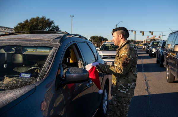 "Capt. Jason Mag, 837th Training Squadron, hands out a candy cane during the morning inbound commute in support of the 37th Training Wing new initiative, ""We Care,"" at Joint Base San Antonio-Lackland, Texas, Dec. 18, 2019. The initiative involved 37th Training Wing military and civilian members spending the morning at various gates letting each person know that they stand together in support of those struggling with depression and thoughts of suicide by holding a positive message of support and handing out over 400 candy canes. If you are struggling with thoughts of suicide, please go directly to the Mental Health Clinic or to your closest Emergency Room. You can also reach the National Suicide Prevention Lifeline at 1-800-273-8255."