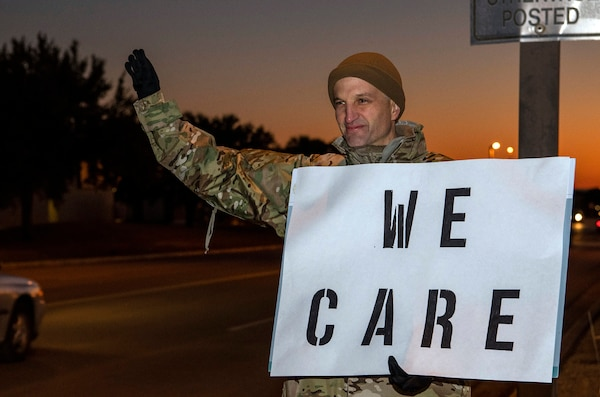 "Lt. Col. Scott Christensen, 331st Training Squadron commander, holds a positive message of support at a base gate during the morning inbound commute as part of their new initiative, ""We Care,"" at Joint Base San Antonio-Lackland, Texas, Dec. 18, 2019. The initiative involved 37th Training Wing military and civilian members spending the morning at various gates letting each person know that they stand together in support of those struggling with depression and thoughts of suicide by holding a positive message of support and handing out over 400 candy canes. If you are struggling with thoughts of suicide, please go directly to the Mental Health Clinic or to your closest Emergency Room. You can also reach the National Suicide Prevention Lifeline at 1-800-273-8255."