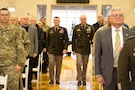 Two generals in green dress uniform walk down center isle.