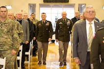 Two generals in green dress uniform walk down center isle.