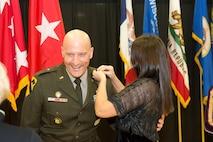 Woman in black dress pinning rank on shoulder of male Soldier in green uniform