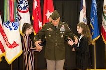 Two young girls stand to each side of male Soldier in green Army uniform
