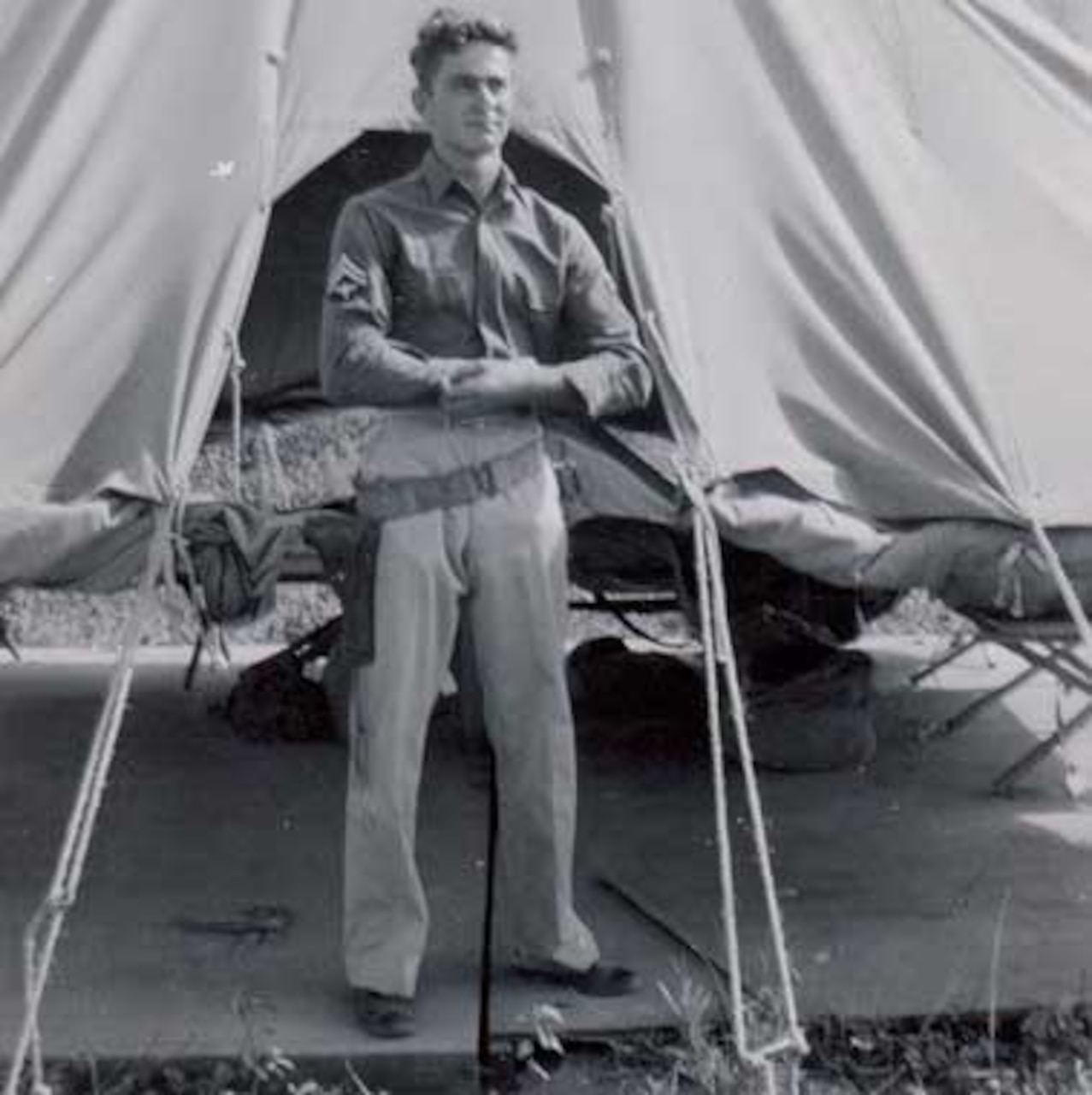A  man poses next to a tent.