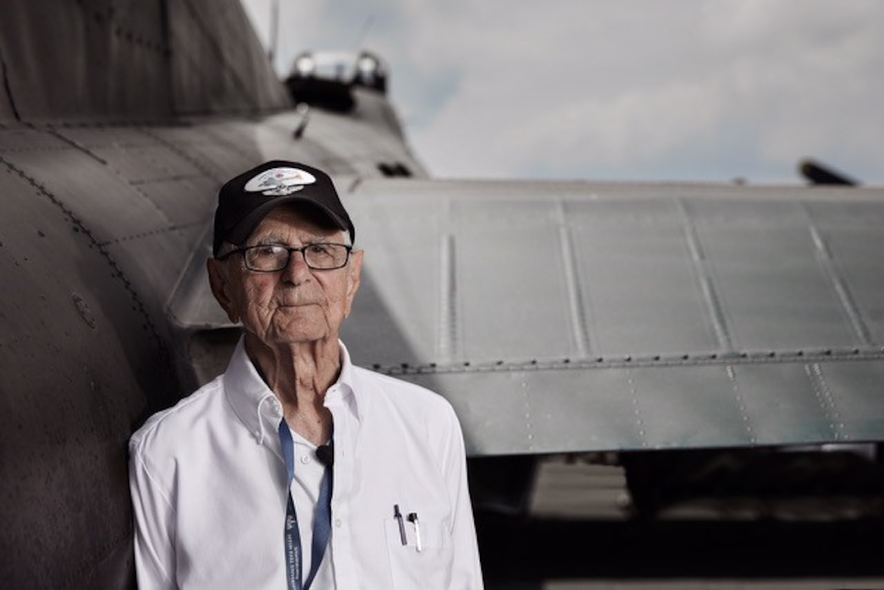 A man poses next to an aircraft.