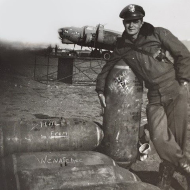 A man poses next to a big artillery shell.