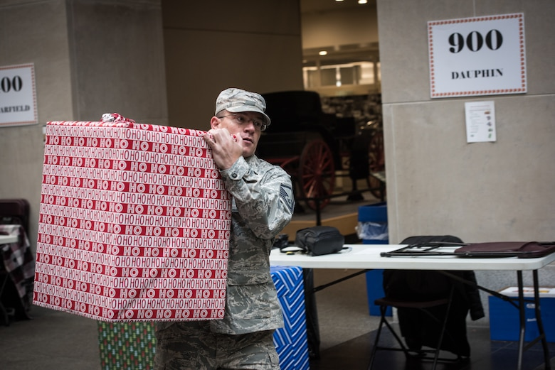 U.S. Air Force Airman Master Sgt. Matt Schwartz, a public affairs specialist with the 193rd Special Operations Wing, Pennsylvania Air National Guard, carries a box of donated-gifts to be loaded onto a truck, during the 30th Annual Holiday Wish Program.