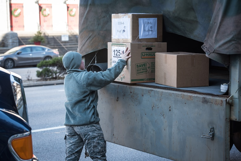 U.S. Air Force Airman 1st Class Emily Harsomchuck, a command post emergency actions controller with the 193rd Special Operations Wing, Pennsylvania Air National Guard, loads boxes of donated-gifts onto a light medium tactical vehicle, during the 30th Annual Holiday Wish Program