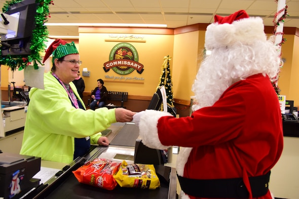 "Sherri Johnshon, Commissary sales store checker, assists Santa Claus in the purchase of some candy from Laughlin's commissary for the nice Airmen he meets during his pre-holiday visit to Laughlin Air Force Base, Texas on Dec. 17, 2019. ""Your commissary offers the quality you expect and the deeper savings you deserve on all the items you will need for your holiday meals, going even further to extend your holiday spending,"" said Tracie Russ, Defense Commissary Agency sales director. ""And while you're at it, use the money you're saving to do your New Year's dinner shopping as well – at the commissary."" (U.S. Air Force photo by Senior Airman Anne McCready)"