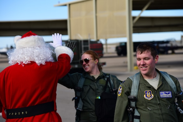 Pilots, returning from a flight, greet Santa Claus on the flightline at Laughlin Air Force Base, Texas, Dec. 17, 2019. As part of an ongoing cooperation between Laughlin and the North Pole, Col. Lee Gentile, 47th Flying Training Wing commander, met with Santa to enhance the base's Specialized Undergraduate Pilot Training program by providing student pilots an opportunity of a lifetime—delivering presents all across the United States. (U.S. Air Force photo by Senior Airman Anne McCready)