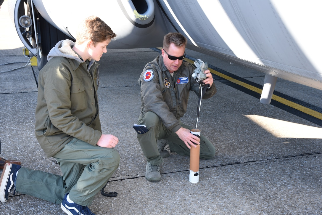 """Lt. Col. Sean Cross, 53rd Weather Reconnaissance Squadron deputy director of operations, demonstrates how a dropsonde works to honorary 2nd Lt. Charles """"Payton"""" Burge, during the Pilot for a Day program Dec. 19, at Keesler Air Force Base, Miss. The 403rd Wing collaborated with Make A Wish Mississippi who selects the children who will participate in the Program. (U.S. Air Force photo by Lt. Col. Marnee A.C. Losurdo)"""