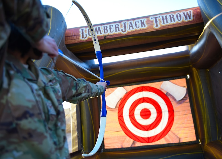 An airman aim a toy bow and arrow