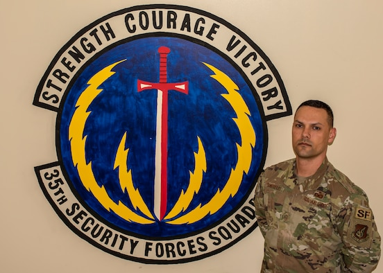 Master Sgt. Andrew Contreras, a 35th Security Forces Squadron chief of standardization and evaluations, pauses for a photo in front of the squadron's insignia at Misawa Air Base, Japan, Dec. 17, 2019. Contreras won the Col. Billy Jack Carter Award by stepping into a detachment superintendent position while deployed in South Korea, working with individuals from different jobs and Pacific Air Force bases. The award honors a security forces member for a specific act, contribution or event. (U.S. Air Force photo by Airman 1st Class China M. Shock)