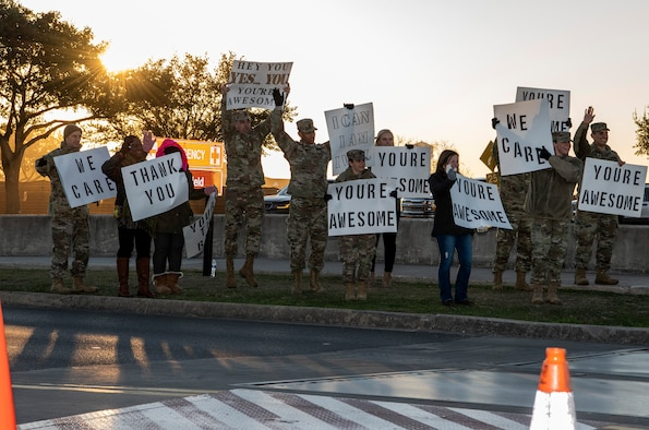 """37th Training Wing military and civilian members hold positive messages of support at base gates during the morning inbound commute as part of their new initiative, """"We Care,"""" at Joint Base San Antonio-Lackland, Texas, Dec. 18, 2019. The initiative involved 37th Training Wing military and civilian members spending the morning at various gates letting each person know that they stand together in support of those struggling with depression and thoughts of suicide by holding a positive message of support and handing out over 400 candy canes. If you are struggling with thoughts of suicide, please go directly to the Mental Health Clinic or to your closest Emergency Room. You can also reach the National Suicide Prevention Lifeline at 1-800-273-8255."""