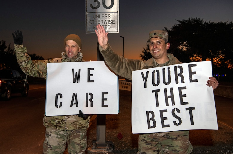 """From left, Lt. Col. Scott Christensen, 331st Training Squadron commander, and Lt. Col. Raymundo Vann, 323rd Training Squadron commander, hold positive messages of support at a base gate during the morning inbound commute as part of their new initiative, """"We Care,"""" at Joint Base San Antonio-Lackland, Texas, Dec. 18, 2019. The initiative involved 37th Training Wing military and civilian members spending the morning at various gates letting each person know that they stand together in support of those struggling with depression and thoughts of suicide by holding a positive message of support and handing out over 400 candy canes. If you are struggling with thoughts of suicide, please go directly to the Mental Health Clinic or to your closest Emergency Room. You can also reach the National Suicide Prevention Lifeline at 1-800-273-8255."""
