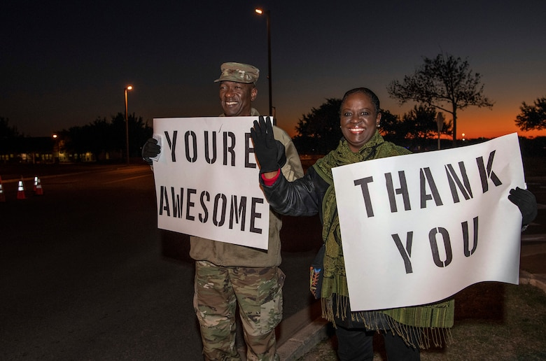 """Col. Isaac Davidson, Inter-American Air Forces Academy commandant, and his wife Lydia hold positive messages of support at a base gate during the morning inbound commute as part of their new initiative, """"We Care,"""" at Joint Base San Antonio-Lackland, Texas, Dec. 18, 2019. The initiative involved 37th Training Wing military and civilian members spending the morning at various gates letting each person know that they stand together in support of those struggling with depression and thoughts of suicide by holding a positive message of support and handing out over 400 candy canes. If you are struggling with thoughts of suicide, please go directly to the Mental Health Clinic or to your closest Emergency Room. You can also reach the National Suicide Prevention Lifeline at 1-800-273-8255."""